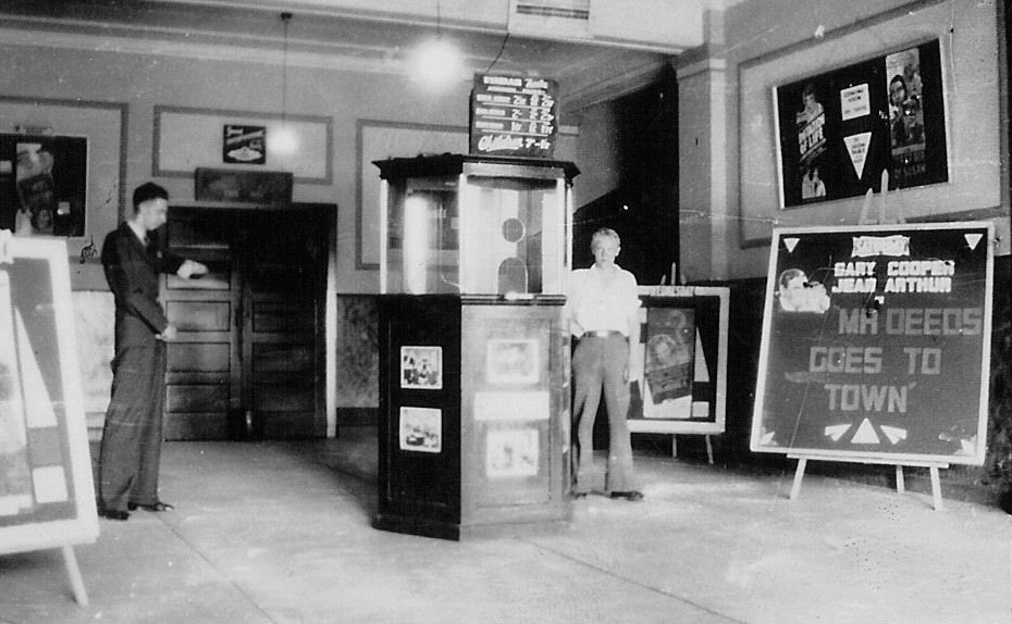 theatre foyer with manager and ticket seller, Mr Deeds showing, 1937